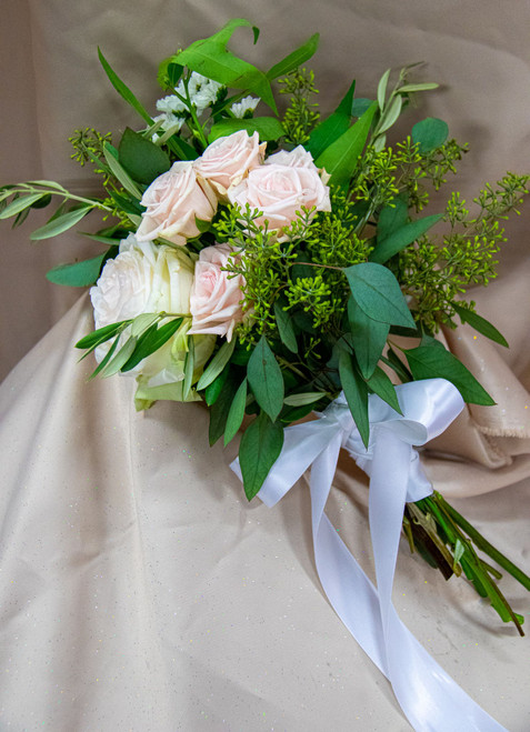 This lovely blend of blush roses with a set of greenery wrapped in a satin ribbon.