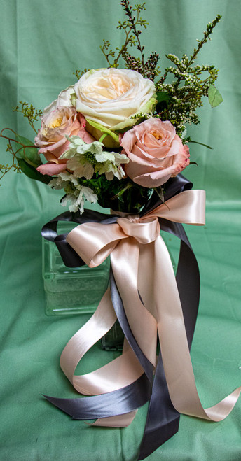 An elegant bridal bouquet  with white and pink roses tied together with ribbon.