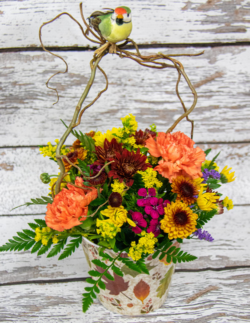 A mixed of fall colored flowers in a melinane pot and accented with curly willow and a bird.