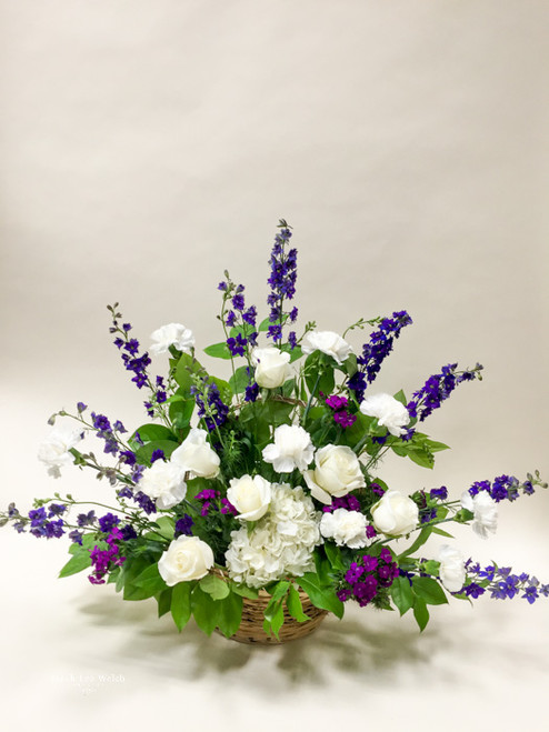 Neutral fresh-cut, long stemmed premium roses and clustered hydrangea accented with purple and blue hues of accent flowers arranged in a woven basket.