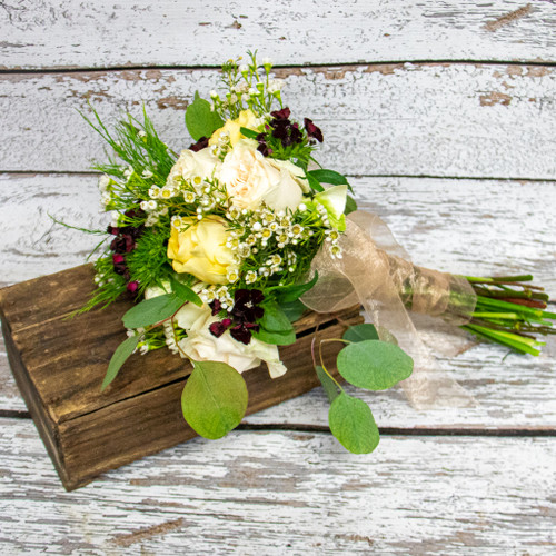 White and pale yellow roses accented with white waxflower and red dianthus in a nosegay style bridal bouquet.