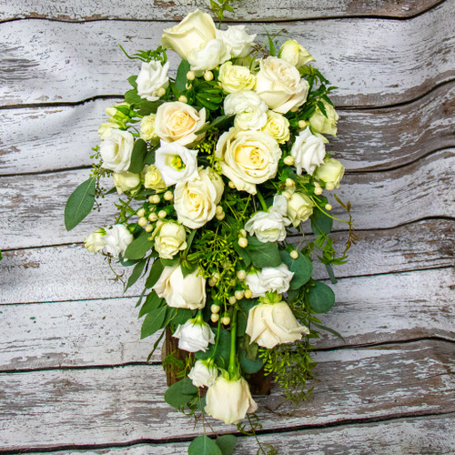 A mixture of ivory roses, white lizenthis, and white hypernicum berries in a cascading style bridal bouquet