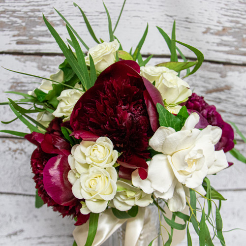 White spray roses with burgundy peonies in a nosegay style bridal bouquet.