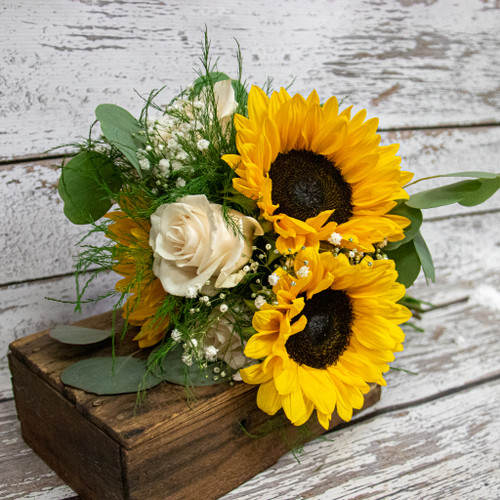 Bright and bold sunflowers accented with greens and white roses arranged in a nosegay style bridal bouquet.