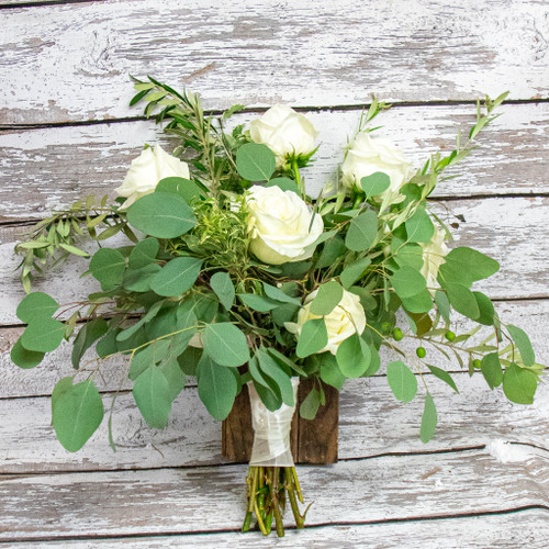 Different types of eucalyptus with a hint of white roses arranged in a hand-tied bridal bouquet.