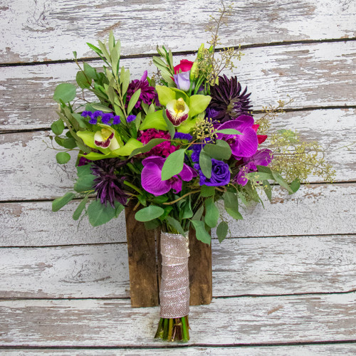 Guaranteed to be a showstopper this bridal bouquet has all the fun colors of pink, purple, fuschia and lime green to make a statement. Wrapped with champagne ribbon in a hand tied wildflower style.