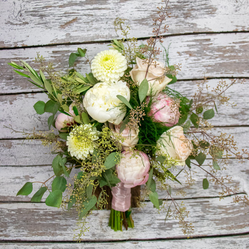 A bridal bouquet with pink and white peonies, white dahalias and soft pink roses designed in a handtied wildflower look.