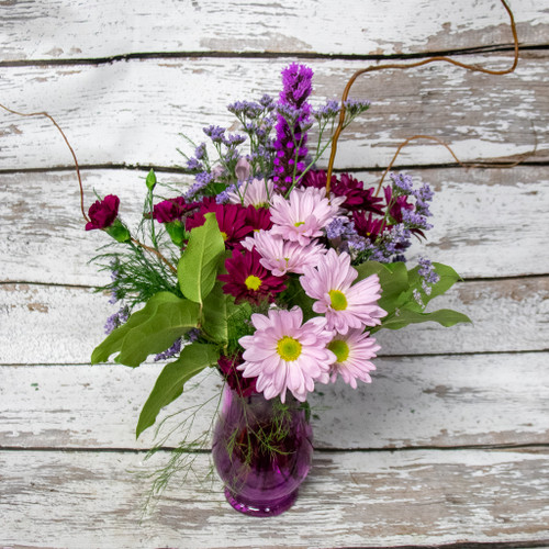 Favorite color purple?  We have the perfect arrangement for you! This arrangement is filled with different shades of purple flowers and a couple pink roses all arranged in a purple vase.