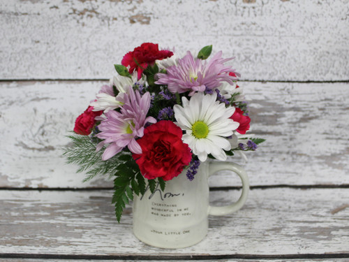 """A ceramic mug that says """"Mom, Everything wonderful I am was made by you """" filled with bright and long lasting flowers."""