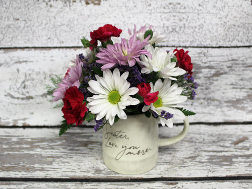 """A ceramic mug that says """"Sister, Love You More"""" filled with bright and long lasting flowers."""
