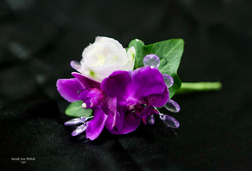 This boutonniere is designed with beautiful bold purple orchids with a touch of white flowers and dazzled in purple bling!