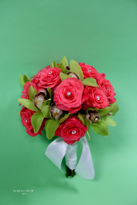 Don't shy away from a little color, with melon colored roses and green cymbidium orchids.