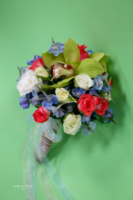 A very sweet bouquet of delphinium, spray roses and the unexpected cymbidium orchid.