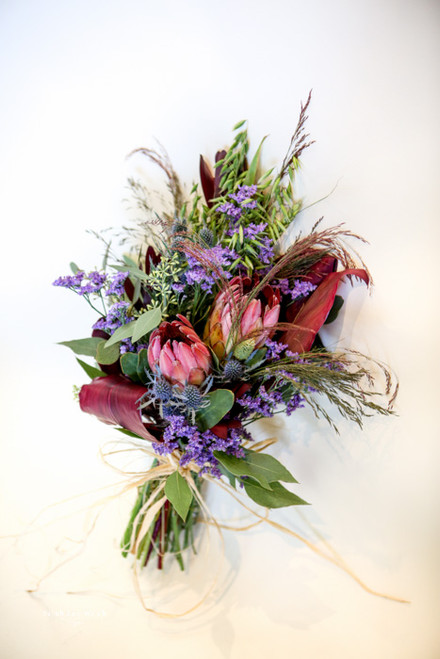 Protea, wild grasses and interesting foliage are in this unexpected handtied bouquet