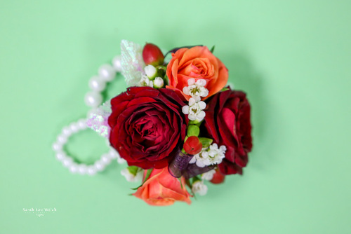 Pearl wristlet, orange and red spray roses, hypericum berries and don't forget the touch of white waxflower!