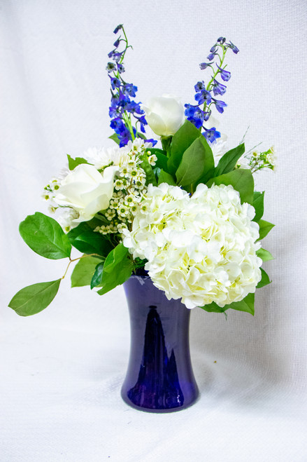 A mixed flower arrangement with blue and white flowers.