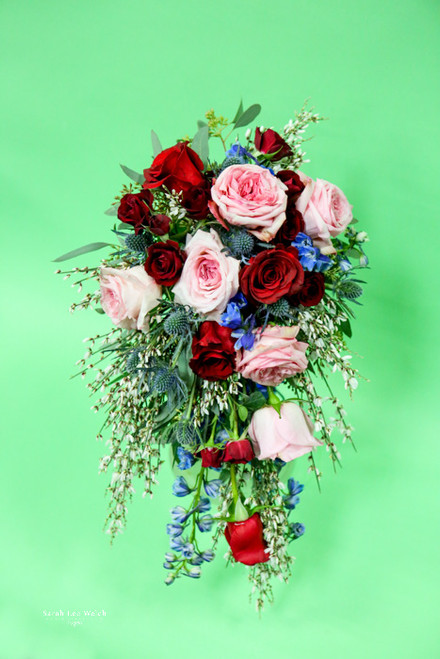 For a romantic spring look of red and pink roses, touch of blue delphinium and thistle and don't forget the fragrant genesta. Subject to availability.