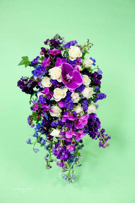 Love purple, you need this in stock, delphinium,  fabulous butterfly orchids and the perfect touch of white roses.