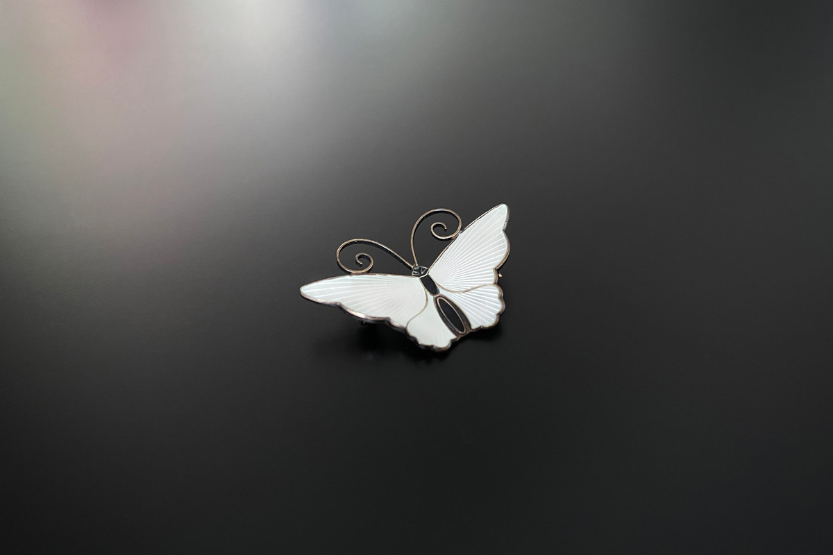 A Classic Norwegian Enamel and Gilt Butterfly Brooch by David Andersen White enamel wings and black body Scrolling antennae Sterling silver gilt Signed to reverse