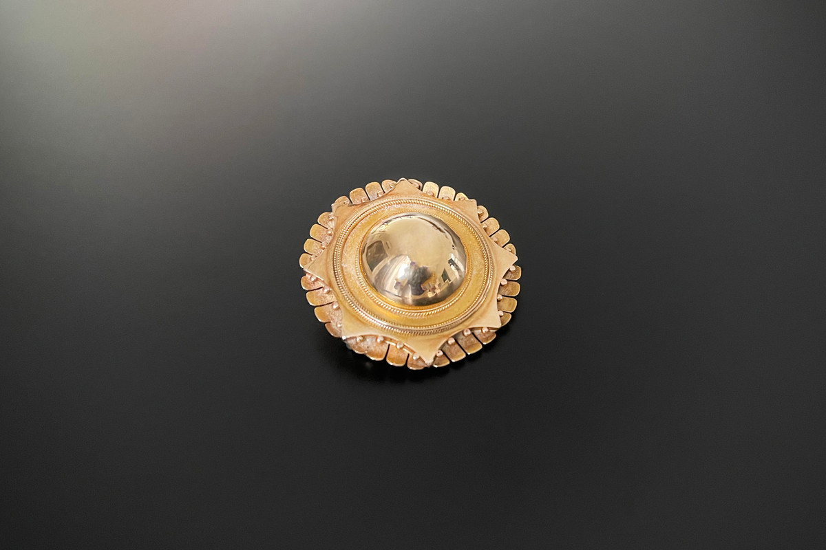 A Bold Gold Target Brooch Circular form Central polished domed pattern with multiple borders of rope twist, beading and fluted decoration Glazed panel to reverse 15ct yellow gold Total weight: 9.9gms Victorian Circa 1870 Dimensions: 35mm x 35mm