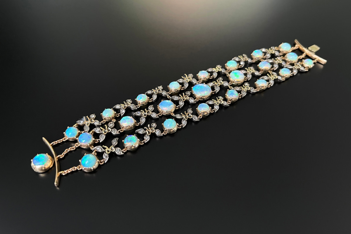 A Fabulous French Naturalistic Opal, Diamond and Gold Bracelet Comprising three rows of graduated round solid white opals cut en cabochon Interspaced with old rose cut diamonds in the formation of butterflies Finished with fine chain and an opal clasp Silver and 18ct gold French hallmarks Total weight: 25.5gms Total length: 175mm Circa 1890