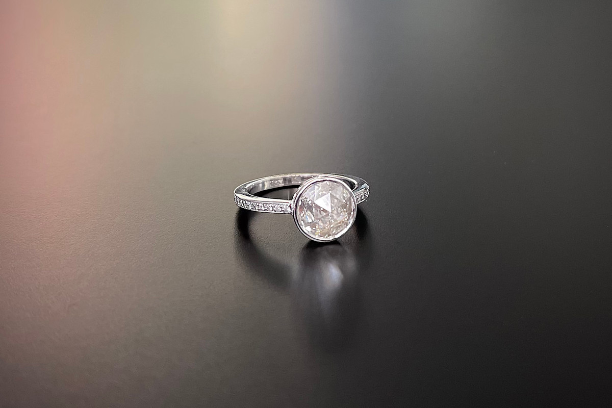 A Striking Diamond Cluster Ring Featuring a rose cut diamond  Bezel set with a halo of small round brilliant diamonds to the gallery and shoulders 18ct white gold Rose cut diamond weight: 1.39cts Total diamond weight: 1.69cts Colour: F-J Clarity: VS-SI Total weight: 4.45gms Size: M