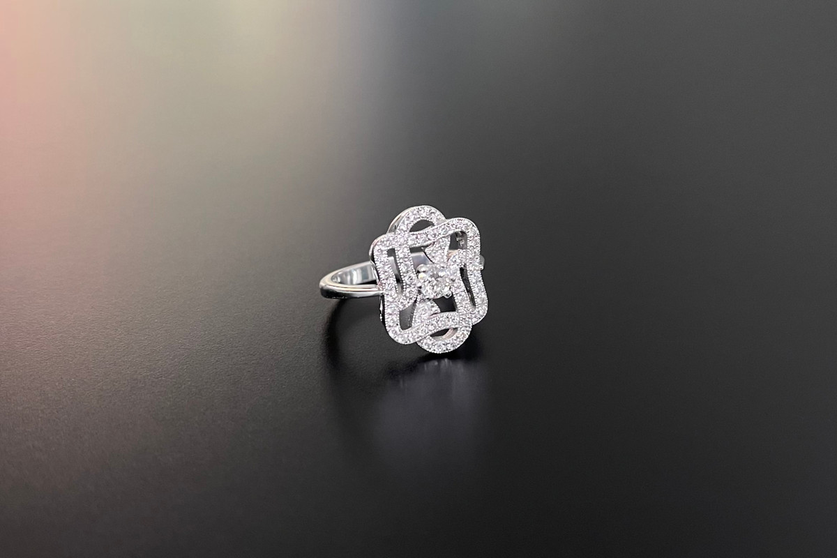 An Elegant Kozminsky Diamond Scroll Ring Central round brilliant cut diamond, surrounded by inter-woven scroll design set with further round diamonds. 18ct white gold. Centre diamond weight: 0.22cts Total diamond weight: 0.58cts  Colour: F-G Clarity: VS-SI Size M.