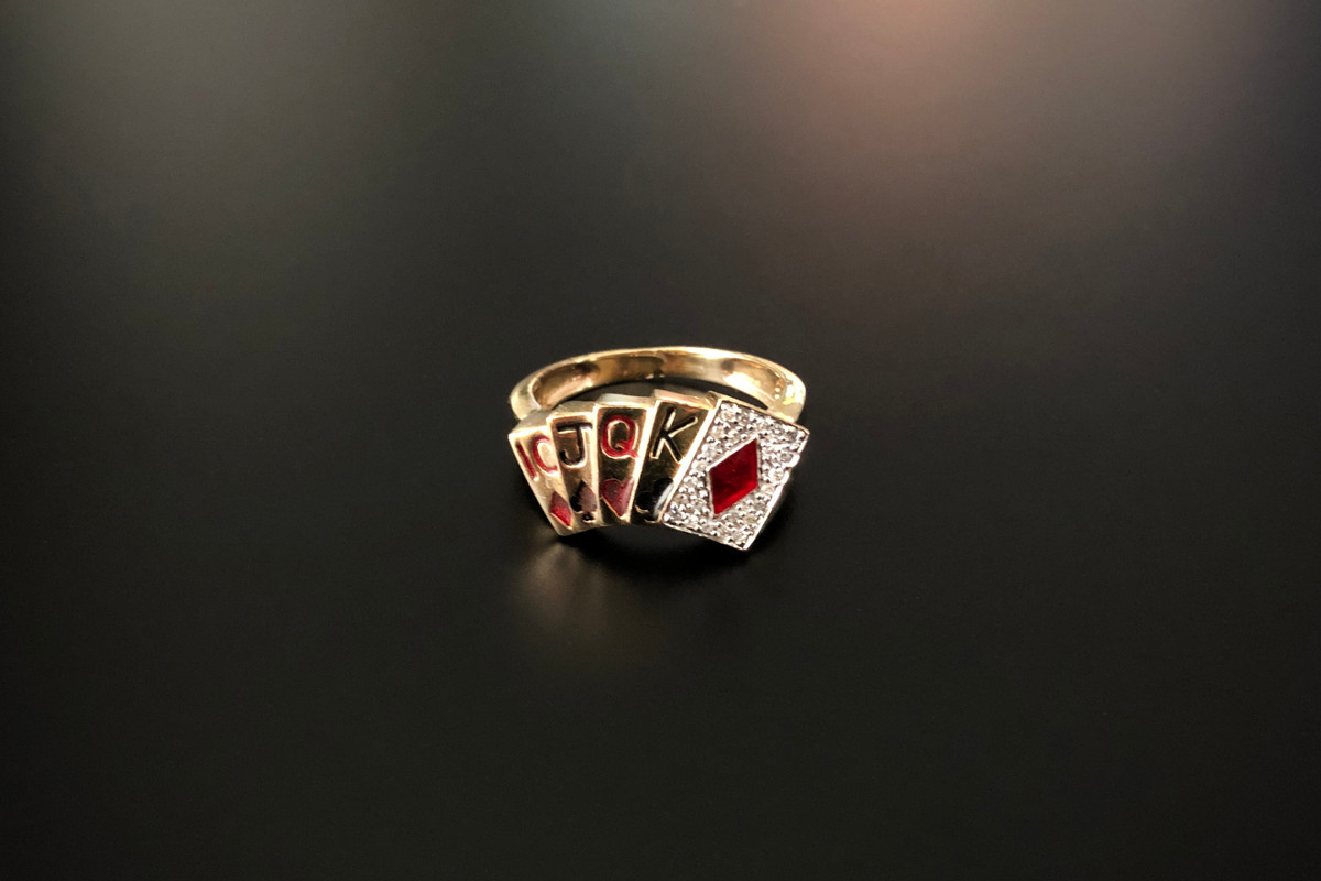 A Fabulous Gold, Enamel and Diamond Ring Modelled as a fan of playing cards Black and red enamel with small diamonds set to the ace of diamonds 10ct gold Total weight: 5.5gms
