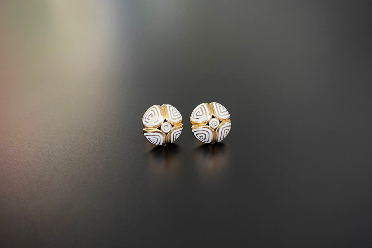 A Divine Pair of Gold and Enamel Earrings Circular form with four petals Overlaid with white enamel geometric patterns. 18ct yellow gold. Post and butterfly back fittings