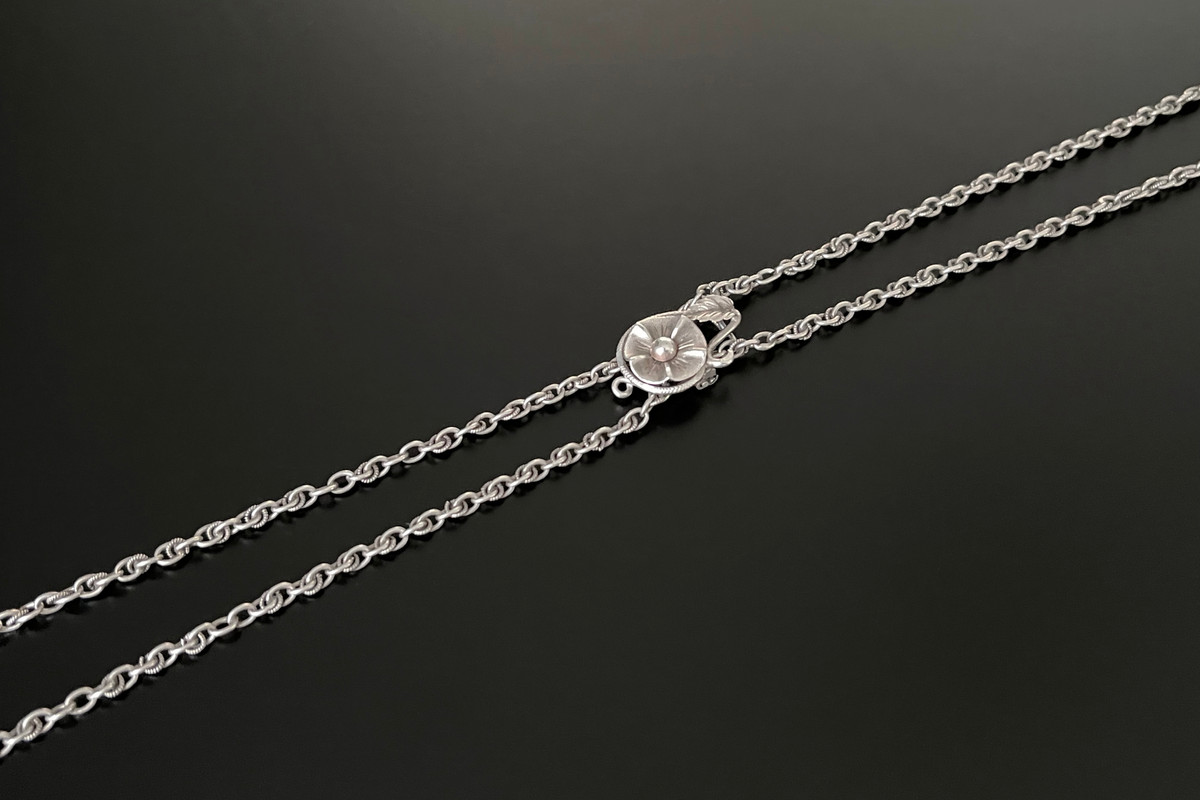 An Elegant French Silver Guard Chain Fancy belcher link chain Having a stylised flower slide Silver Total weight: 22.80gms Total length: 1440mm Antique Circa 1900