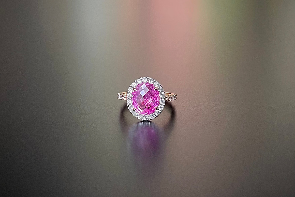 A Fabulous Pink Sapphire and Diamond Ring Cluster form Central oval chequerboard cut pink sapphire surrounded by small round brilliant cut diamonds in a halo and to the shoulders. 18ct rose gold. Sapphire weight: 3.62cts Total diamond weight: 0.75cts Colour: G-H Clarity: VS-SI
