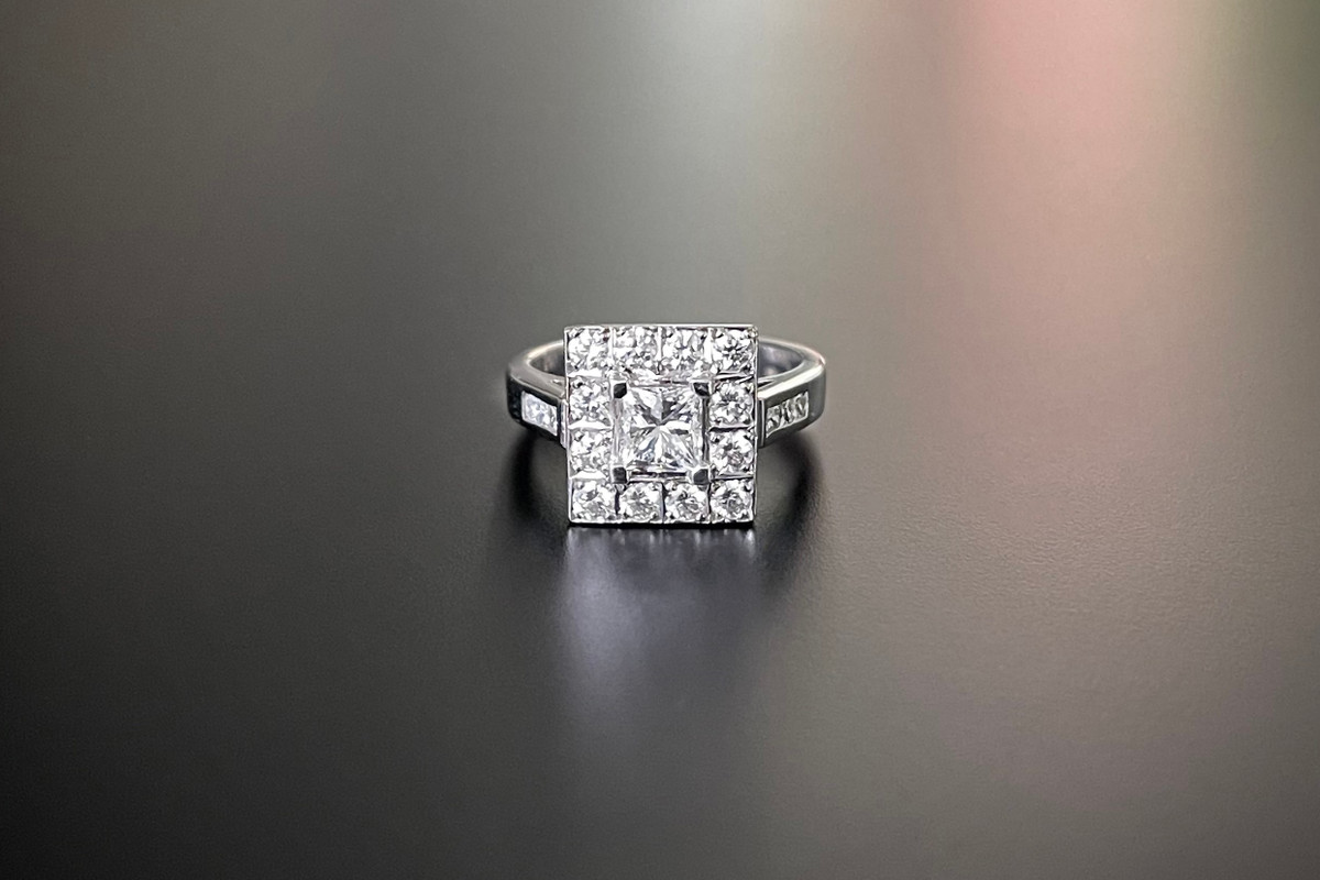 A Smart Diamond Plaque Ring Square form Centrally set with a princess cut diamond Surrounded by a border our round brilliant cut diamonds and further smaller diamonds to the shoulders 18ct white gold Total diamond weight: 1.56cts Colour: G-H Clarity: VS-SI