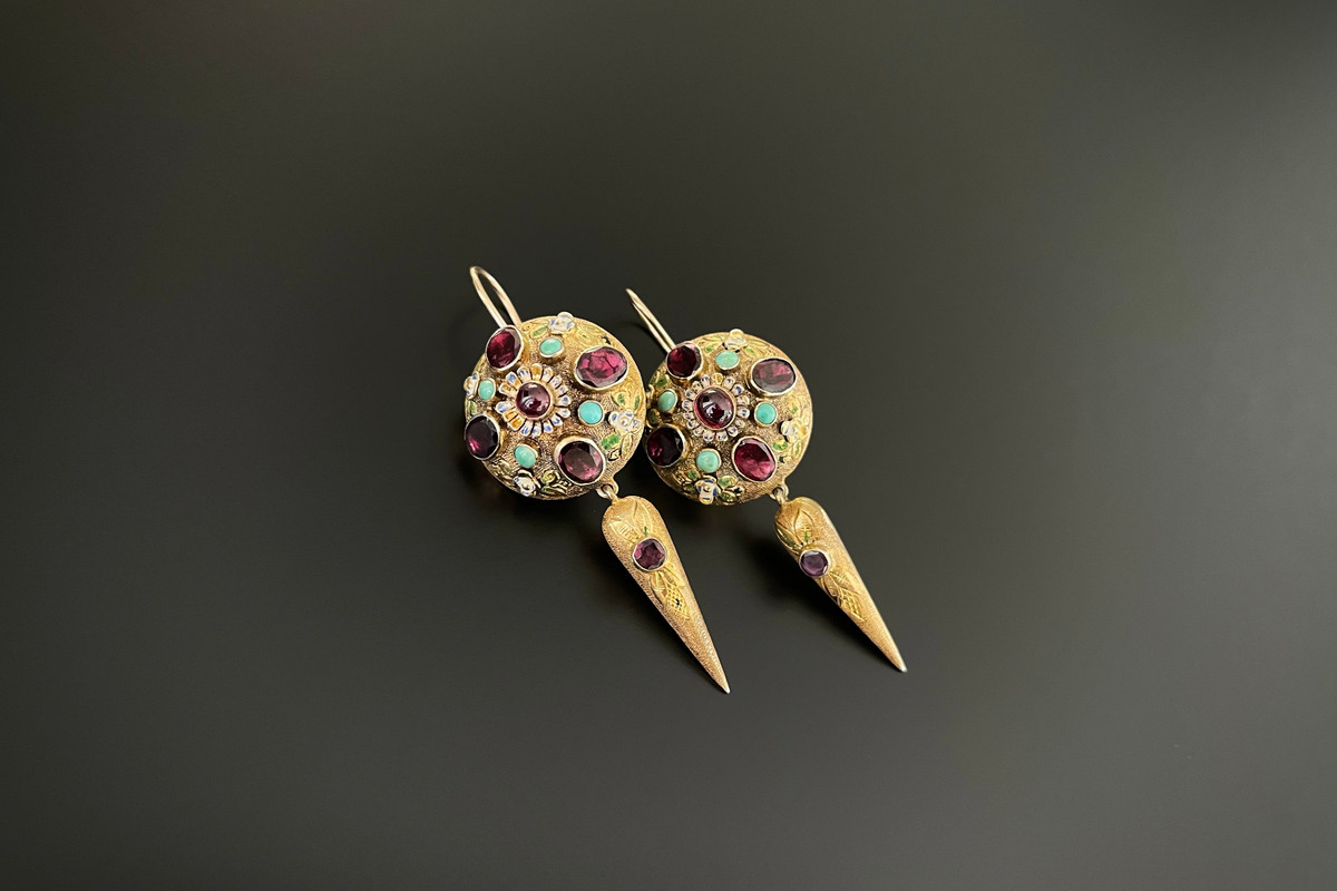 A Stricking Pair of Austro Hungarian Earrings Comprising domed panels and an elongated drop set with foiled back garnets and turquoise. Having enamel highlights throughout. 9ct gold hook fittings. Silver gilt Circa 1900 Dimensions: 23mm x 60mm