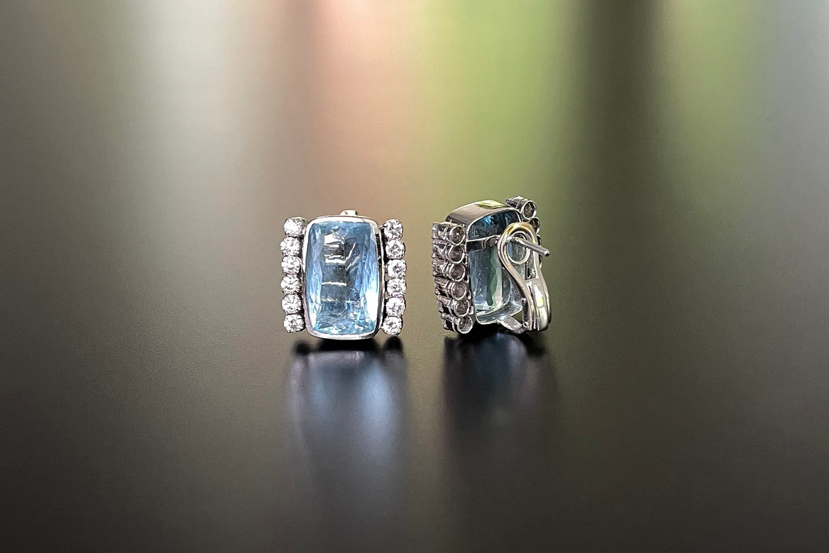 A Stylish Pair of Aquamarine and Diamond Earrings  Each cushion cut aquamarine bezel set. Flanked by a row of six round brilliant cut diamonds claw set to each side. 18ct white gold. Total aquamarine weight: 17.00cts Total diamond weight: 1.60cts Colour: H Clarity: VS-SI Post and clip fittings.