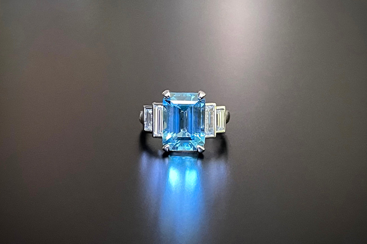 A Stunning Kozminsky Aquamarine and Diamond Ring Comprising an Emerald Cut aquamarine, basket set with four claws. Accompanied with two graduating Baguette Cut diamonds, bezelled set to the shoulders. Aquamarine weight: 5.12cts Total diamond weight: 0.98cts, E-F, VVSI-VSI Total weight: 8.24gms 18ct white gold Size: N