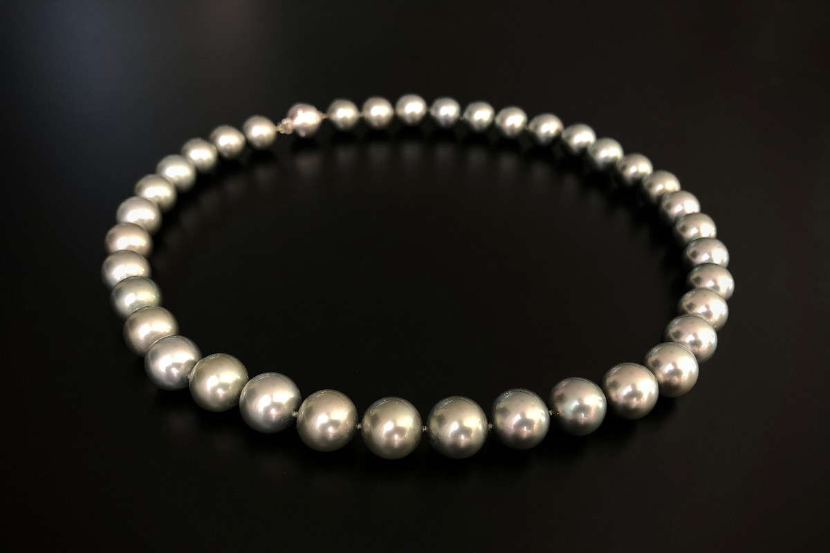 Thirty seven round pearls of silver, grey and soft green hues of fine lustre, measuring 11.5mm to 11.8mm  18ct brushed white gold ball clasp with round brilliant cut diamonds totalling 0.13cts.  Polished brushed finish.  Total length 490mm.