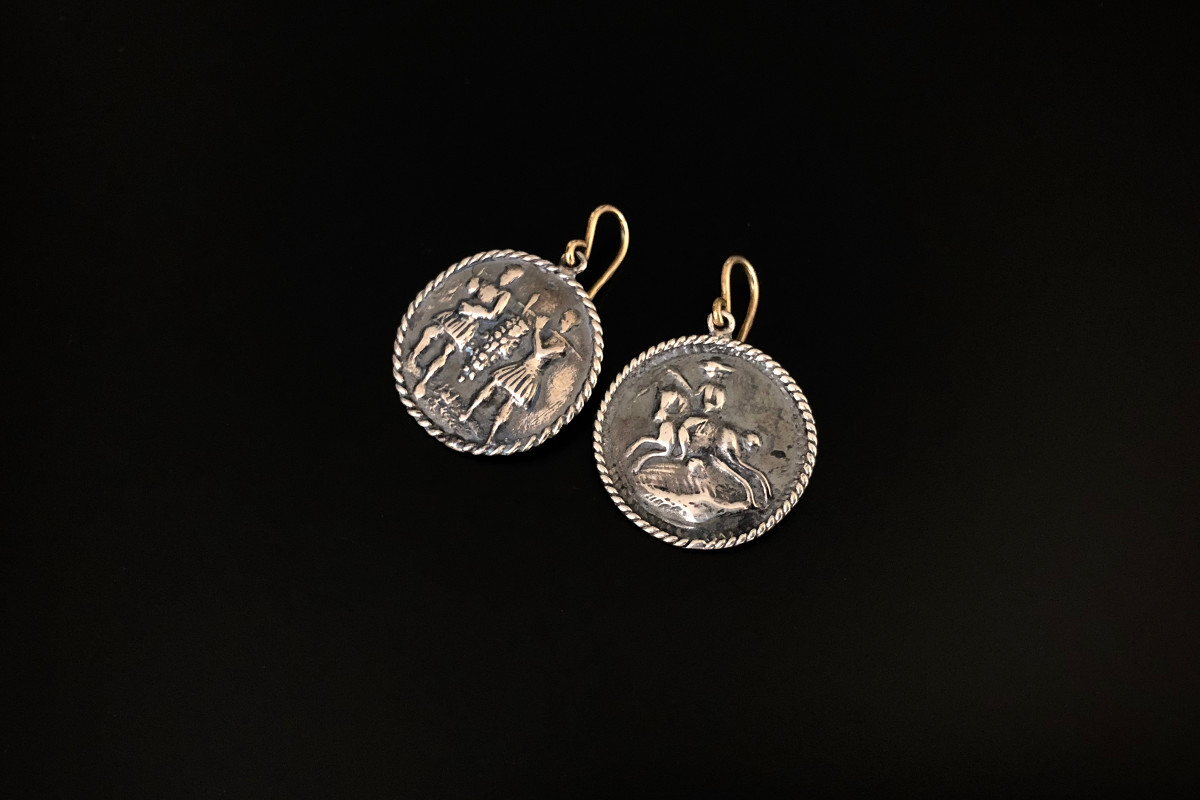 Circular form earrings with figural scenes with a rope twist border SIlver