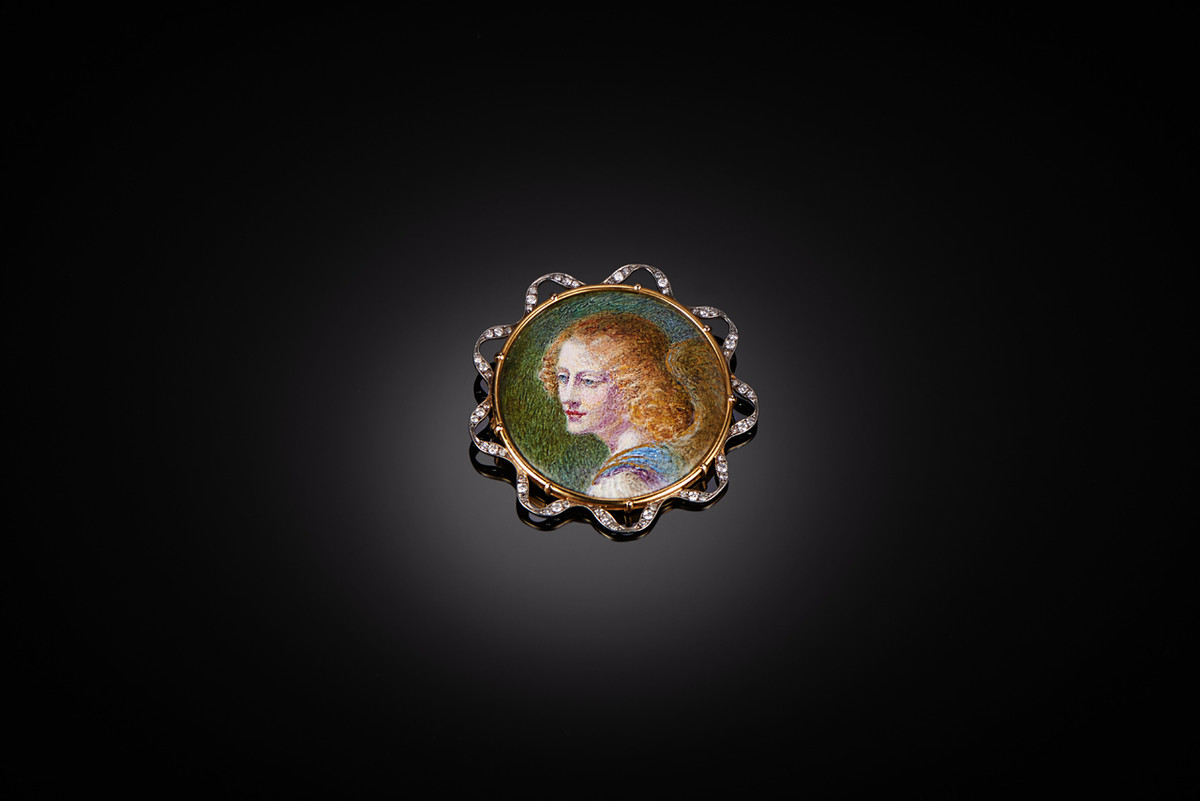 A Rare Enamel and Diamond Brooch depicting a portrait of a winged Pre Raphaelite maiden. Gold ribbon border set with diamonds.