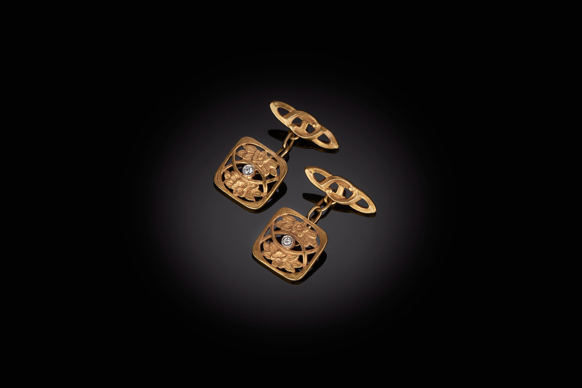 Gold Art Nouveau cufflinks Square pierced form with scroll foliate design Set with an early round brilliant cut diamond Smaller confirming terminals 18ct yellow gold