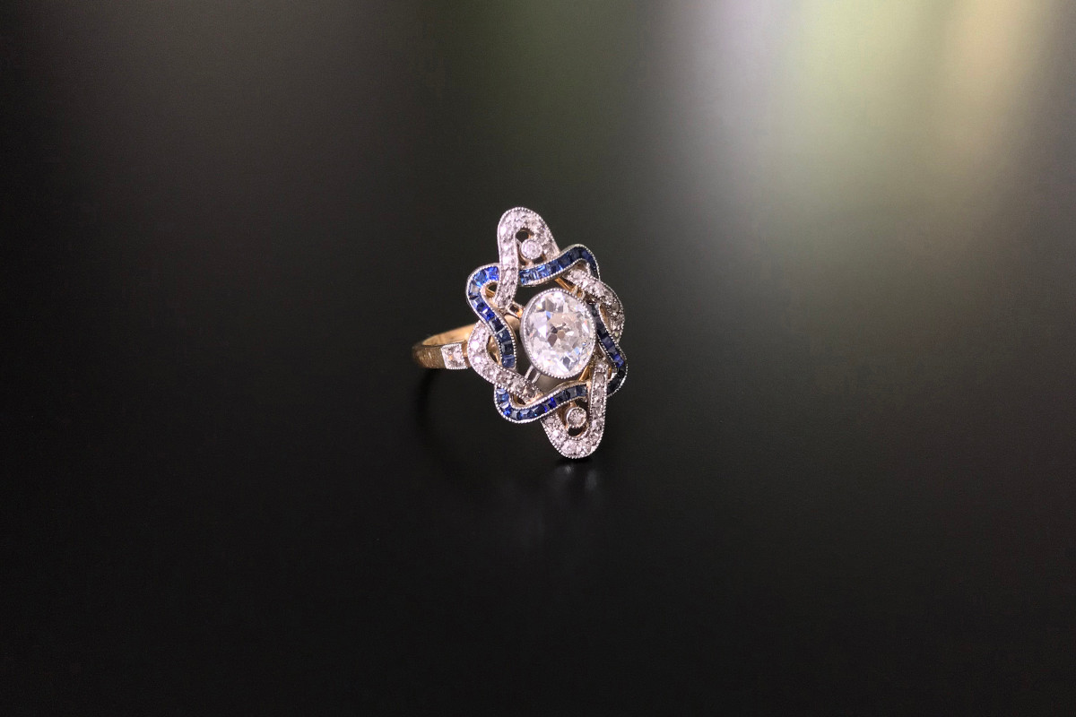 Sapphire and diamond plaque ring, Oval Old European cut diamond and bezel set Surrounded by woven ribbon design set with square cut sapphires and Old Cut diamonds. 18ct yellow gold.
