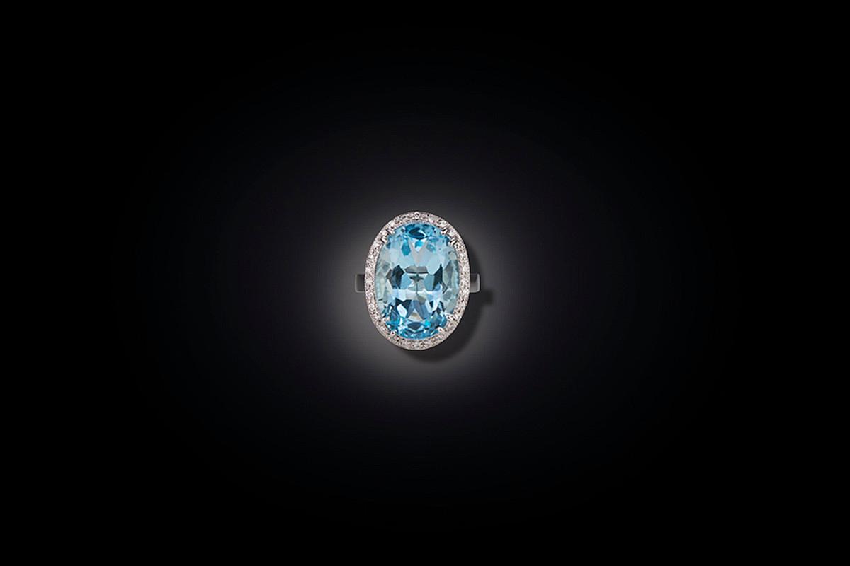 Aquamarine and Diamond Ring Oval cut aquamarine surrounded by a halo of twenty eight round brilliant cut diamonds 18ct white gold