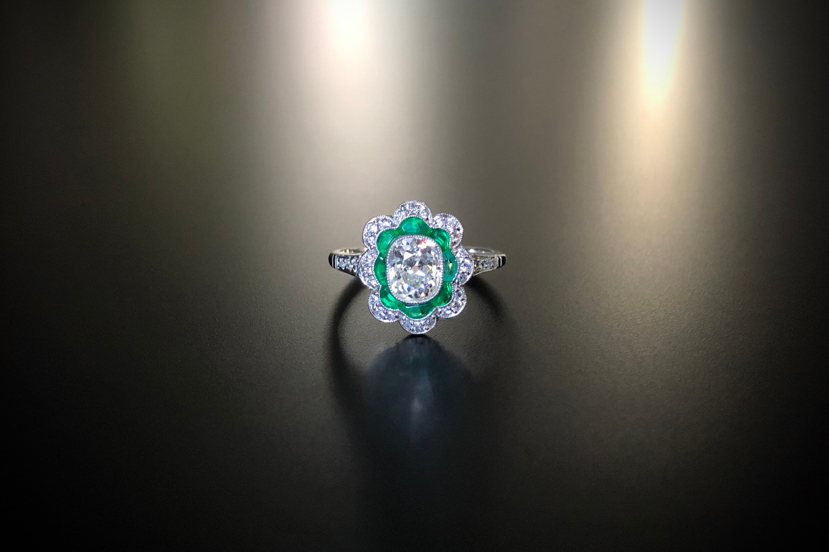 Diamond and emerald ring with oval cushion cut diamond surrounded by a scalloped border of emeralds and an outer row of round brilliant cut diamonds. Principal diamond: 1.05cts Platinum