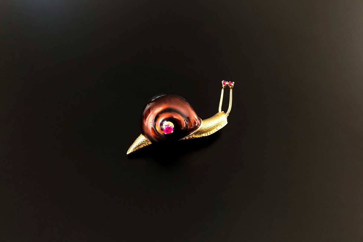 Modelled as a snail, brown enamel shell, textured gold body and finished with a round ruby to the shell and the eyes 18ct yellow gold