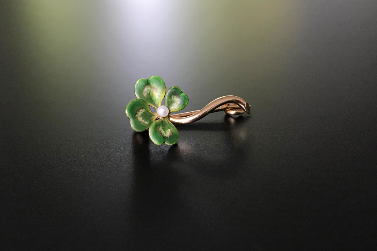 Four Leaf Clover Gold and Enamel Brooch Matt enamel green petals set with a central seed pearl on a curved gold stem 14ct yellow gold Circa 1890