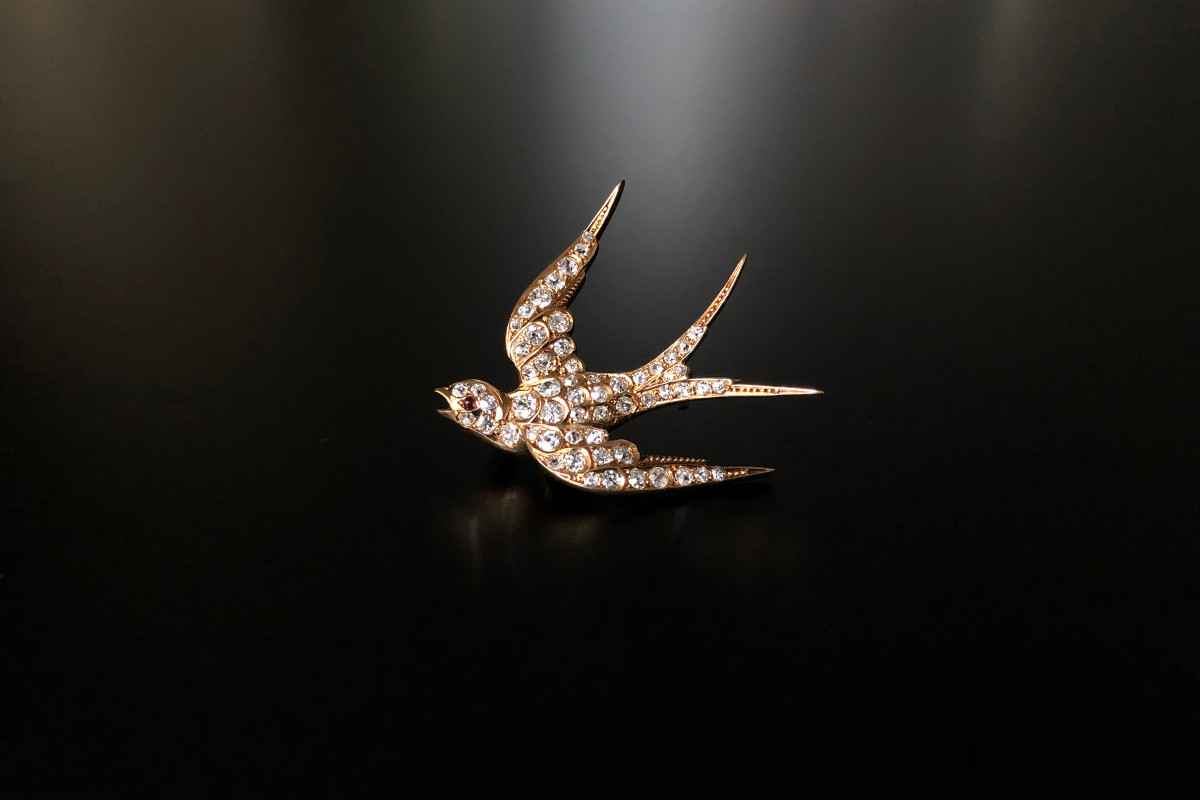 Diaond swallow brooch Set throughout with old European cut diamonds and finished with a small cabochon ruby eye Total diamond weight 1.95cts 18ct gold