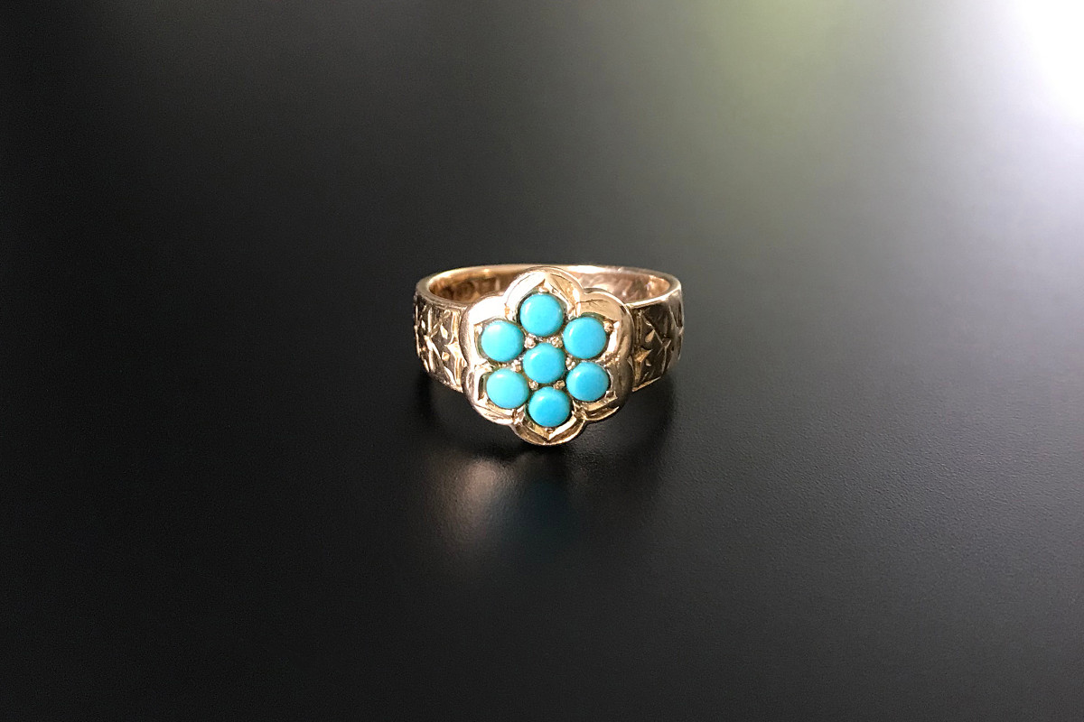Turquoise and Gold Ring Flat gypsy design Seven small turquoise in a flower cluster formation Carved chevron detail to shoulders  18ct yellow gold Hallmarked Birmingham 1879 Victorian