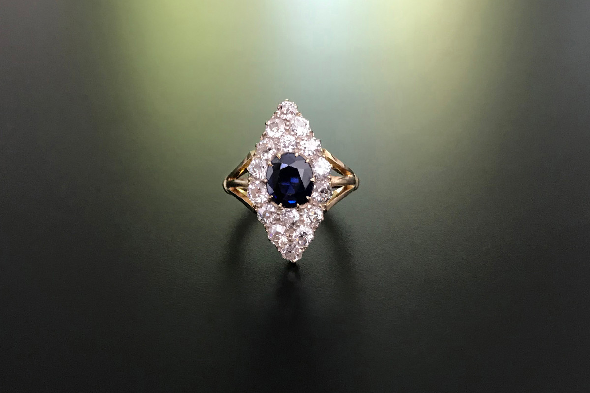 Sapphire and Diamond Plaque Ring Lozenge panel centrally set with an oval cut sapphire Surrounded by round old European cut diamonds Claw set Triple split shoulders 18ct yellow gold Total weight: 4.35gms Sapphire weight: 1.45cts Total diamond weight: 1.60cts Antique  Circa 1900