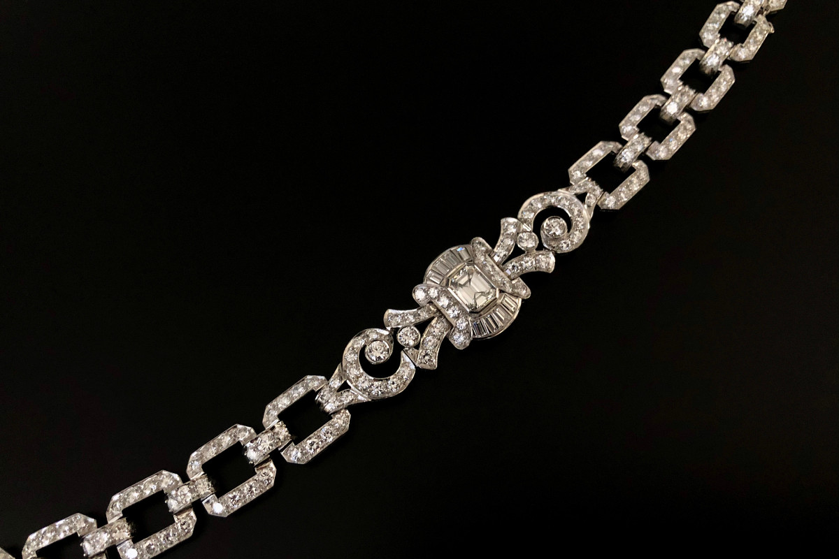 Diamond Bracelet Emerald cut diamond surrounded by round brilliant and tapered baguette cut diamonds, flanked by diamond set fancy links and ten square cut links and nine smaller diamond links Platinum
