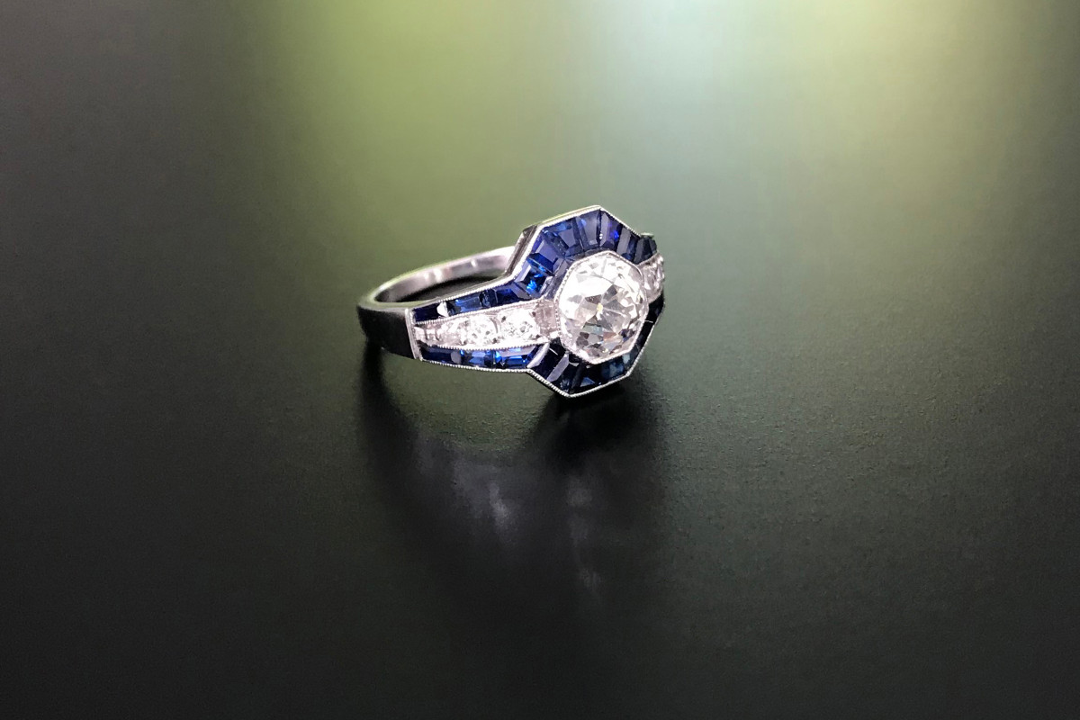 Diamond and Sapphire Ring Old European cut diamond in hexagon frame  Surrounded by fancy cut dark blue sapphires and further diamond detail to the shoulders Platinum Principal diamond: 1.40cts Total diamond weight: 1.60cts Colour: I-J Clarity: VS-SI Sapphire weight: 1.10cts Platinum Art Deco
