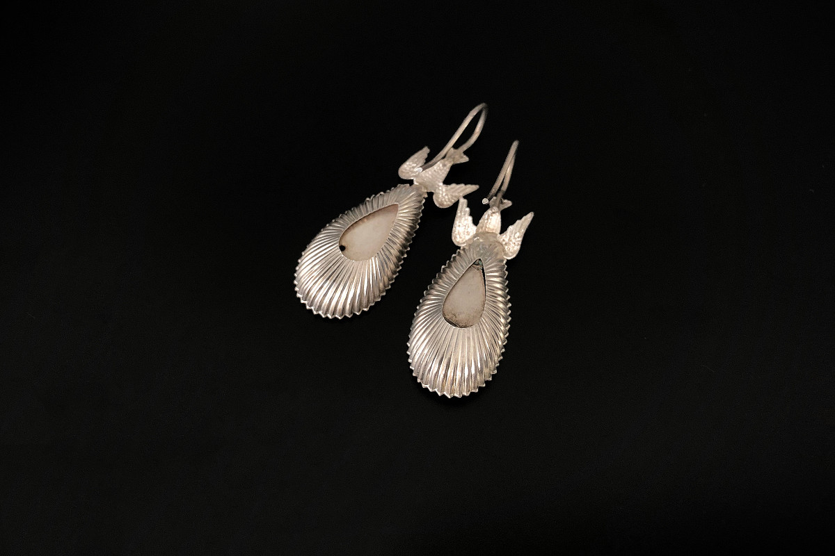 Victorian sIlver earrings Featuring a descending bird motif suspended with a pear shaped fluted and polished panel below Hook fittings Silver Circa 1890